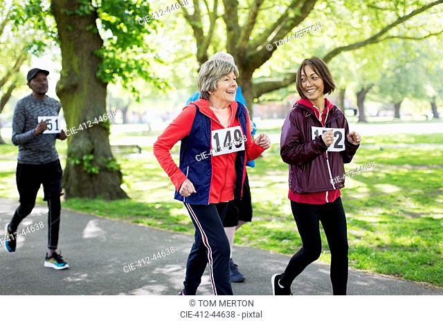 Active senior women friends power walking sports race in park