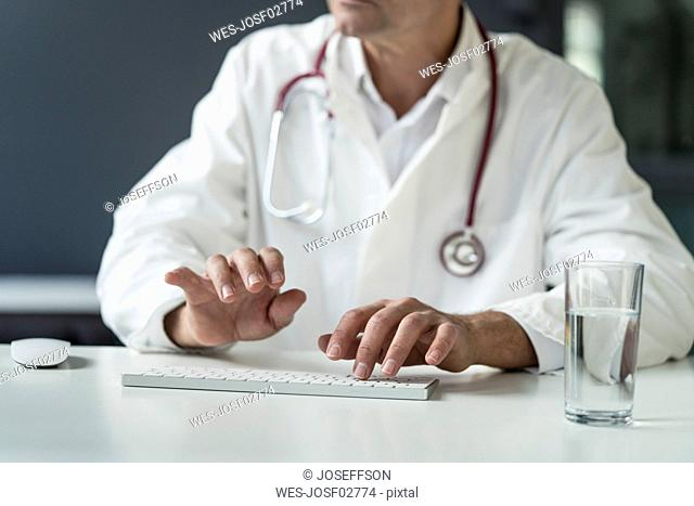 Close-up of doctor in medical practice typing on keyboard at desk