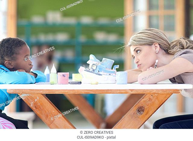 Teacher and girl pouting at each other across table