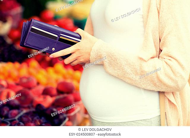 sale, shopping, pregnancy and people concept - close up of pregnant woman with wallet and and credit cards buying food at street market
