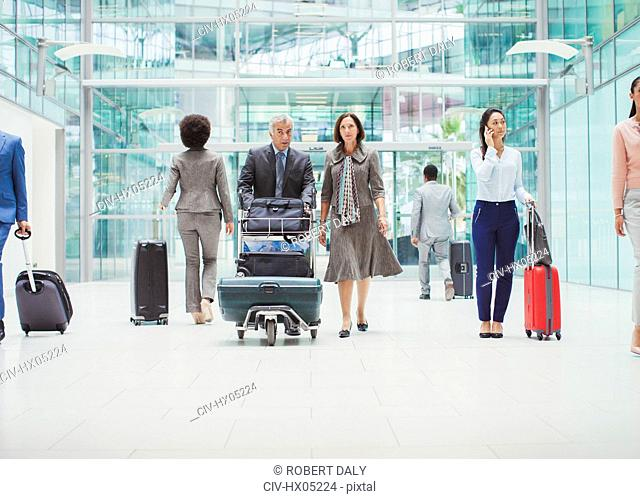 Business people walking with luggage in airport