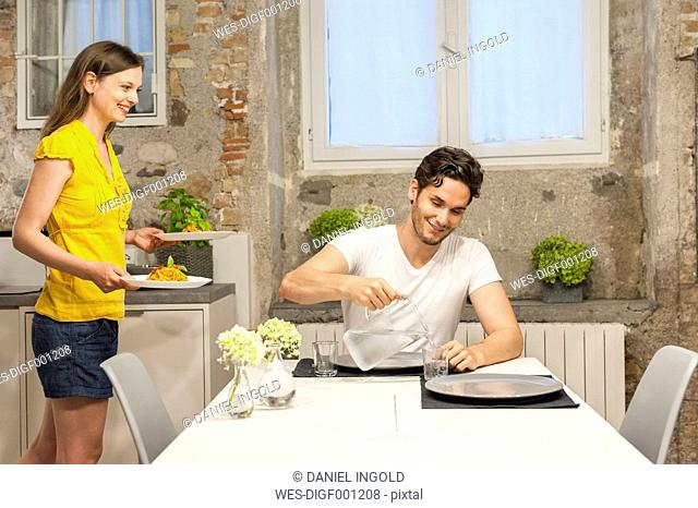 Couple in kitchen eating pasta