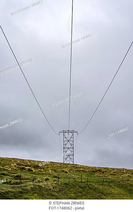 Low angle view of electricity pylon on green field against cloudy sky, Highlands, Iceland