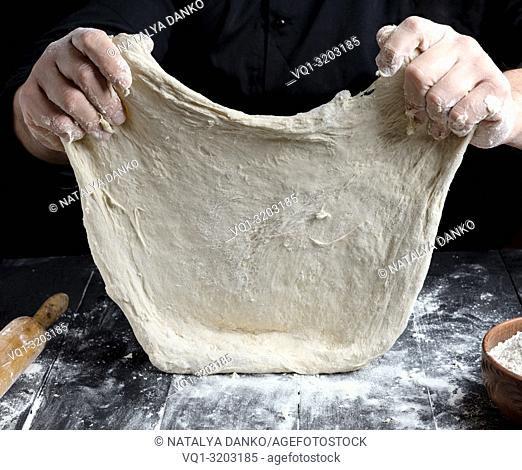 Chef in black jacket, kneads dough from white wheat flour, close up