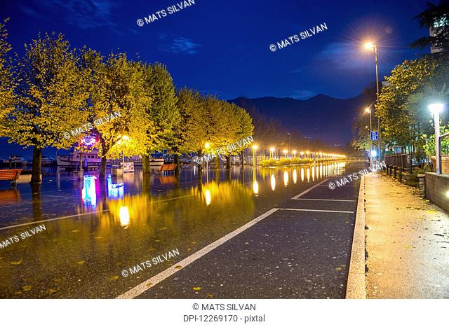 Reflection of lights and trees in the water due to flooding of Lake Maggiore; Locarno, Ticino, Switzerland