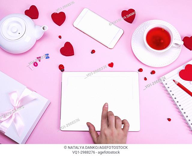 female hand touches the screen of an electronic tablet with a white screen on a pink background, near a cup of tea and a smartphone with a white blank screen