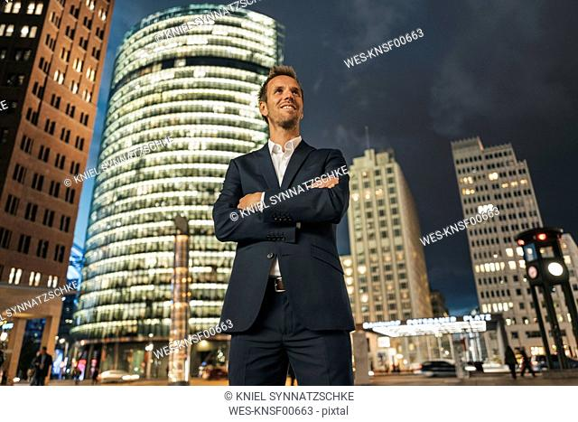 Germany, Berlin, smiling businessman standing in front of Potsdamer Platz at night