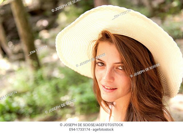 A happy 20 year old brunette woman wearing a white top and a floppy straw hat in a forest setting looking directly at the camera