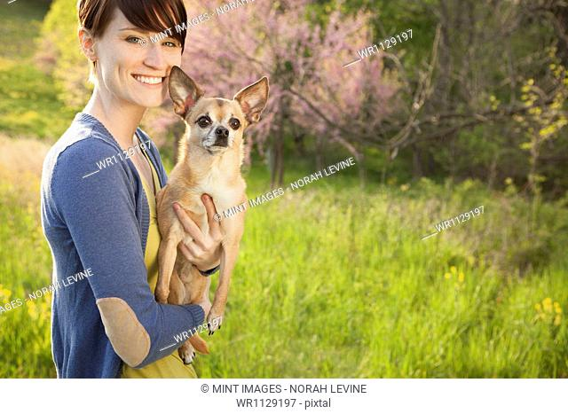 A young woman in a grassy field in spring. Holding a small Chihuahua dog in her arms. A pet
