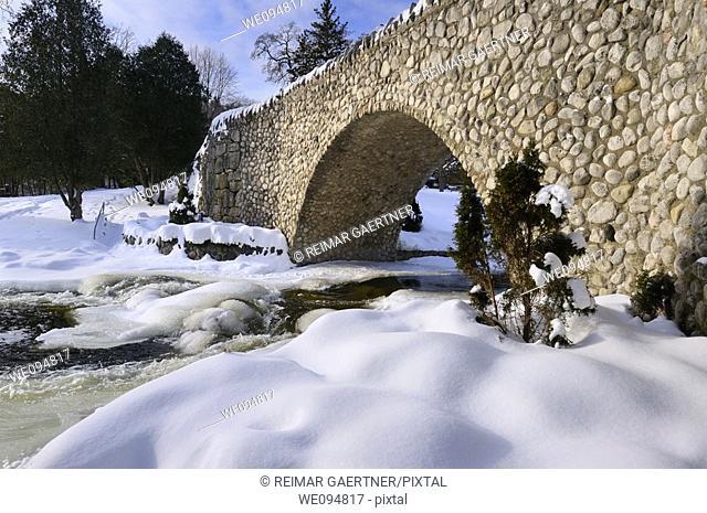 Spencer Creek running under a stone bridge at Webster Falls Conservation Area Park in winter
