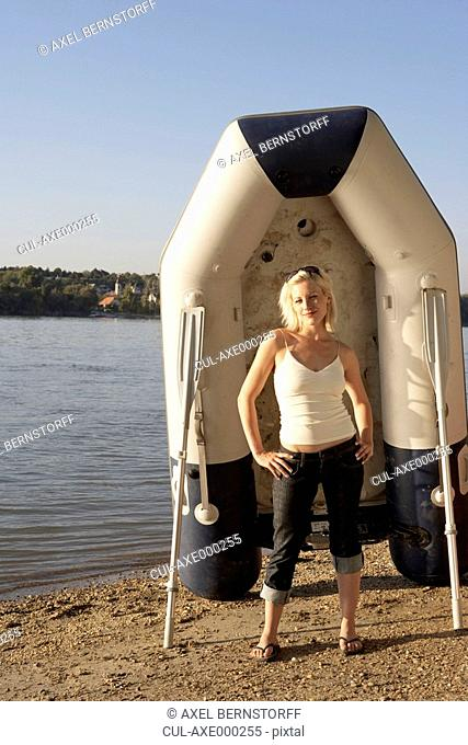 Woman standing on a beach with a raft and oars smiling