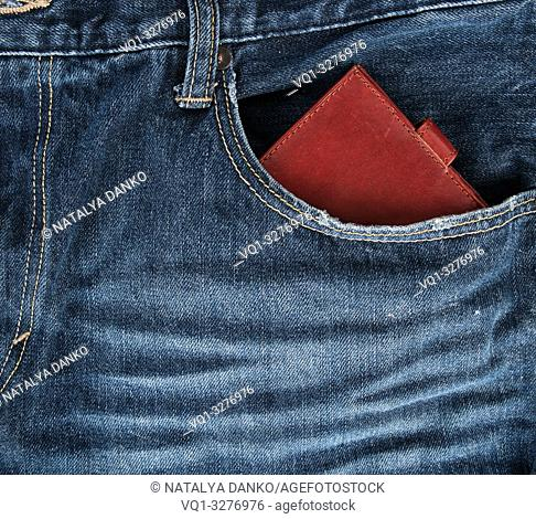 Brown leather wallet in the front pocket of blue jeans, full frame