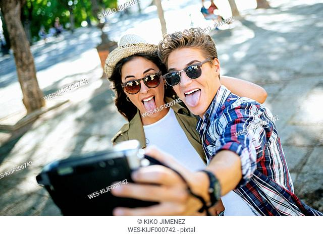 Young couple sticking out tongues while taking selfie with camera