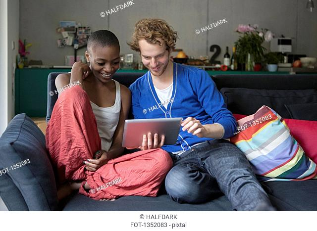 Smiling friends using digital tablet together on sofa at home