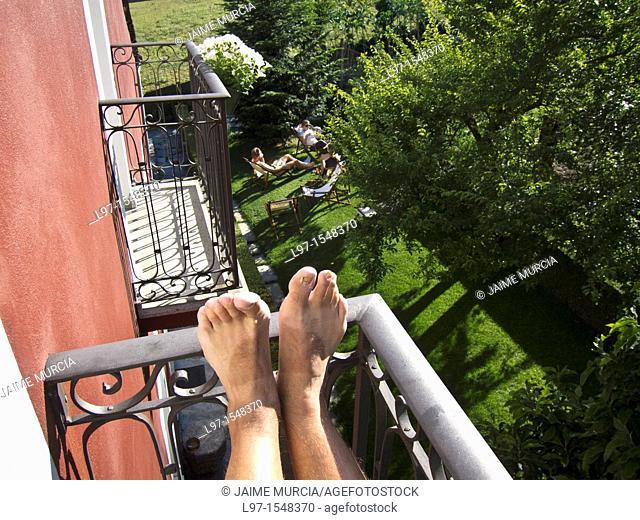 Feet on balcony rail