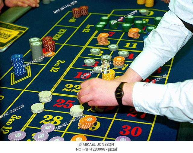 A dealer arranging chips at the roulette table