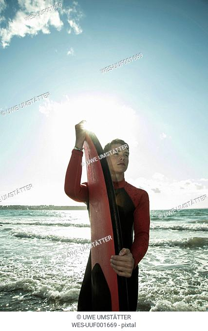 France, Brittany, Camaret-sur-Mer, teenage boy with surfboard at the ocean