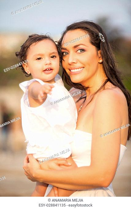 Mother and her baby girl dressed in white
