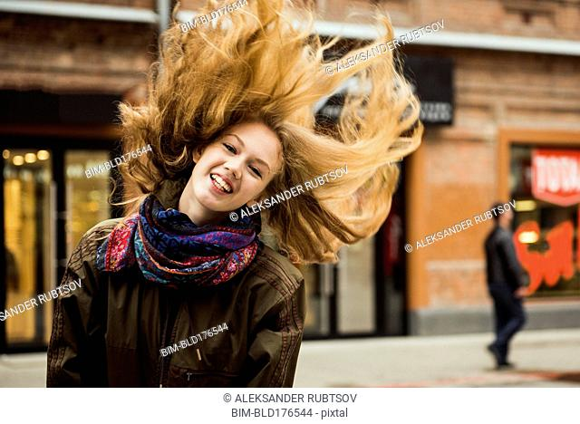 Caucasian woman tossing hair outdoors