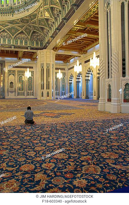 Lone muslim praying, kneeling on the world's largest single carpet, in the main hall of the Sultan Qaboos Grand Mosque, Muscat, Oman