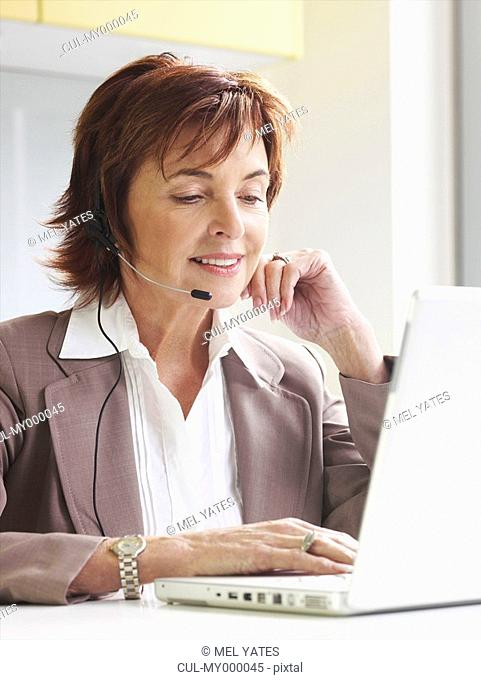 Senior woman with headset on laptop