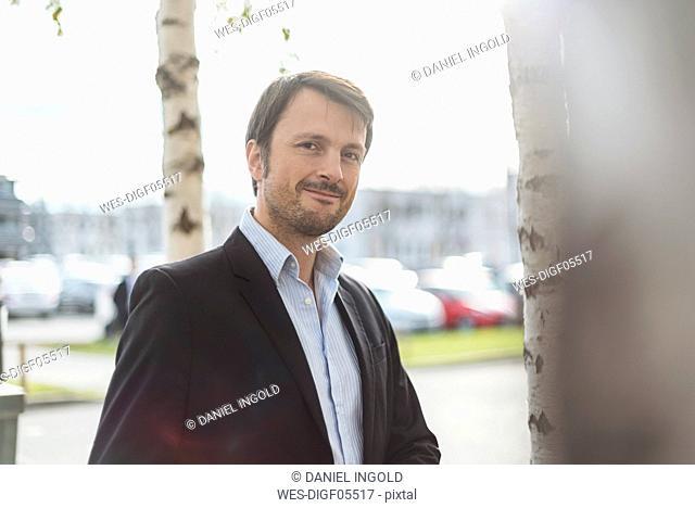 Portrait of a businessman under trees