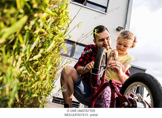 Father and daughter repairing bicycle together