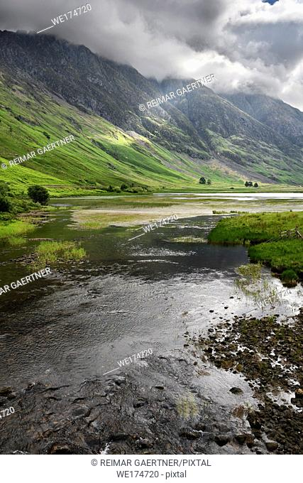 Loch Achtriochtan on the River Coe with dappled sun on the steep Aonach Eagach Ridge mountains in clouds Glen Coe Valley Scotland