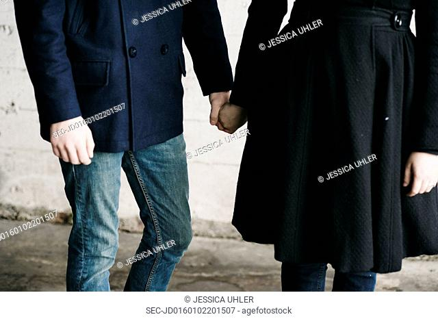 Mid section of young couple holding hands