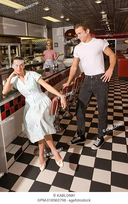 Young woman rolling her eyes at young man in old-fashioned diner, waitress in background