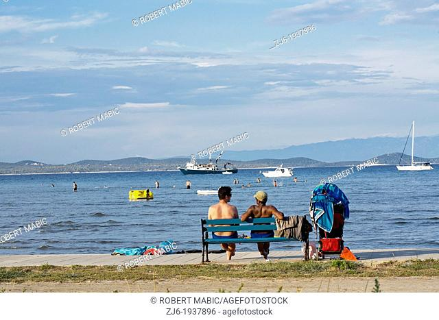 2 friends sitting on a bench by the sea waiting for transport. Adriatic sea Island of Susak Croatia
