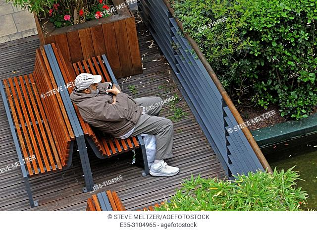 A man sits alone reading his mobile messages. Beziers, France