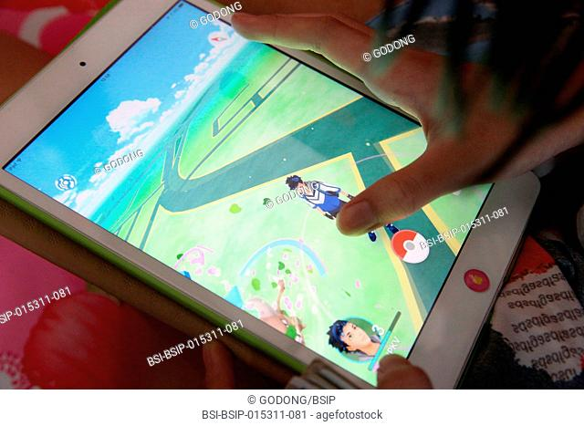 Girl playing with her tablet during a Pokemon Go gaming