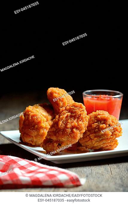 Fried chicken bites and sweet sauce on wooden table
