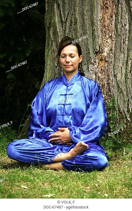 Chan Mi Qi Gong - inner smiling - woman wearing a blue kimono in the nature doing exercise fŸr relaxation - against stress , abnormal attitude , hardening