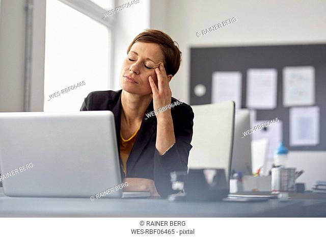Businesswoman sitting in office, having a headache