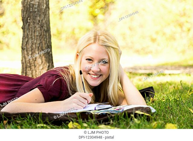 A young woman doing homework outdoors while enjoying a warm autumn day in a park and posing for the camera; Edmonton, Alberta, Canada