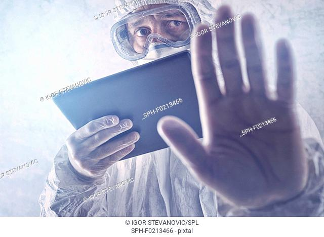 Scientist in protective suit with digital tablet