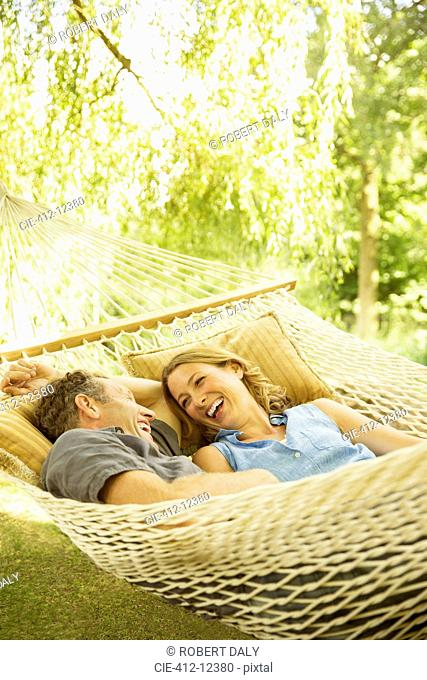 Couple relaxing in hammock outdoors