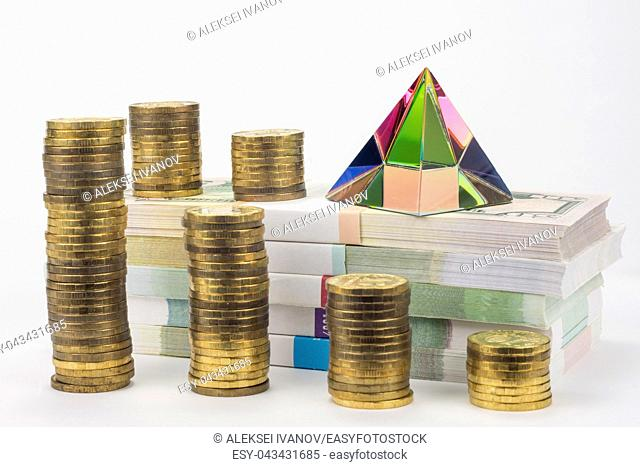 Stacks of coins, bundles of notes and a glass pyramid