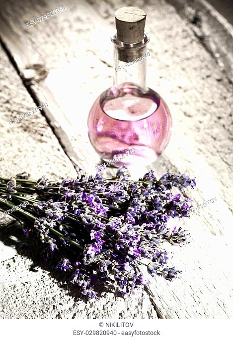 Spa background with bunch of lavender and bottle with aromatherapy oil on a white wooden background