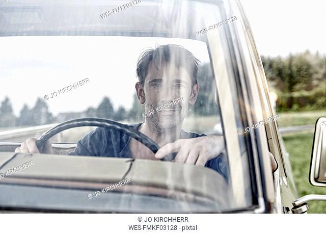 Smiling man driving Pick Up