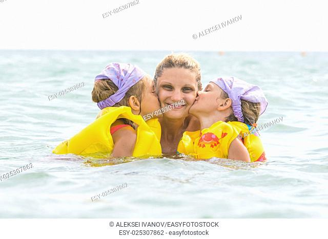 Daughters kiss mom swimming in the sea