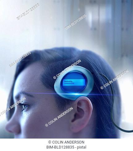 Mixed race woman undergoing futuristic brain scan