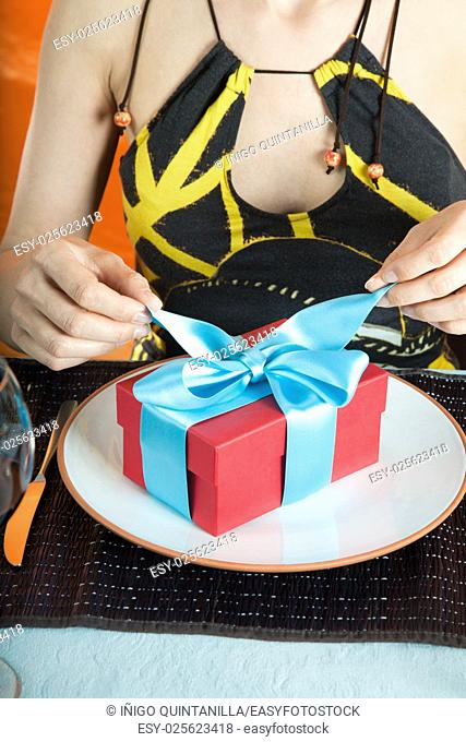 woman with brown and yellow dress opening blue bow of gift red present box with hands, over white dish in table of restaurant