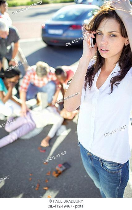 Woman calling emergency services at car accident