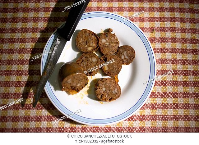 Blood sausage made from Spanish Iberian pigs, the source of Iberico ham known as pata negra, and a knife sit on a plate in a home in Prado del Rey