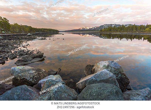 Sunset and sky reflecting in water and big rocks in the foreground, mountains in the background has strings of snow on them, Stora sjöfallets national park