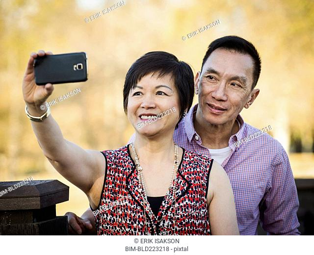 Older Chinese couple taking selfie outdoors