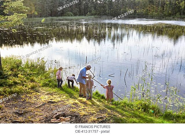 Grandfather teaching grandchildren fishing at sunny lakeside